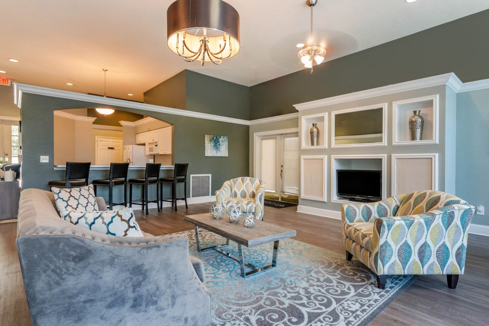 Resident clubhouse with fireplace, couch, two chairs, coffee table, rug and bar stools