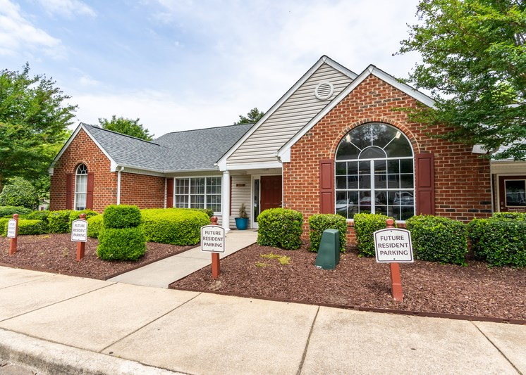 The Leasing Office building is made of brick and tan siding and has multiple windows. There is a large flower bed in front with mulch and bushes. A sidewalk leads to the front door and there is parking out front reserved for future residents.