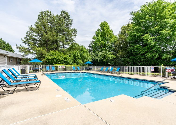 The swimming pool is a large rectangle surrounded by an expansive sundeck with lounge chair seating. The pool furniture is a cool blue and includes lounge chairs, three umbrella, and three round tables. The pool is enclosed by a white fence and is surrounded by large grassy areas and trees.