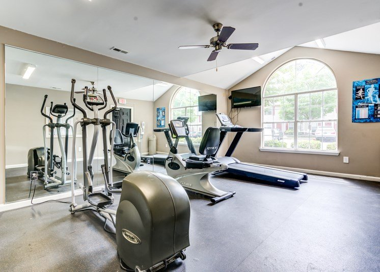 The fitness center has tan walls, rubberized flooring, a large picture window, a ceiling fan and a tv mounted on the wall. It is equipped with a treadmill, a stationary bicycle and an elliptical machine.