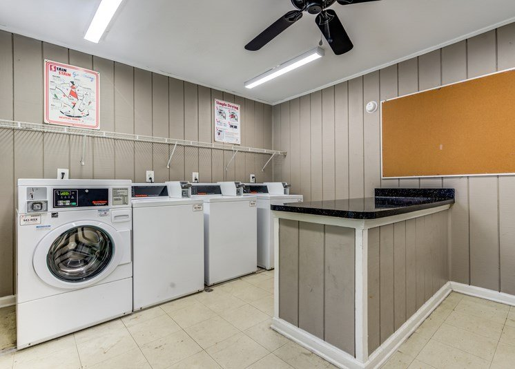 The community laundry room has gray panel walls with white trim, tile flooring and a ceiling fan. It features washing machines and dryers for resident use