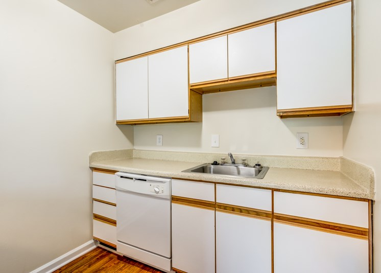 A vacant kitchen with hardwood style flooring, white walls, white cabinets with light wood trim, light countertops, a single sink and a white dishwasher