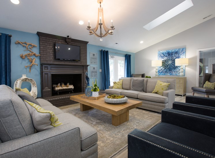 Clubhouse Lounge with Grey Couches Dark Grey Armchairs Blonde Wood Coffee Table Surrounding Brick Fireplace with Mounted TV