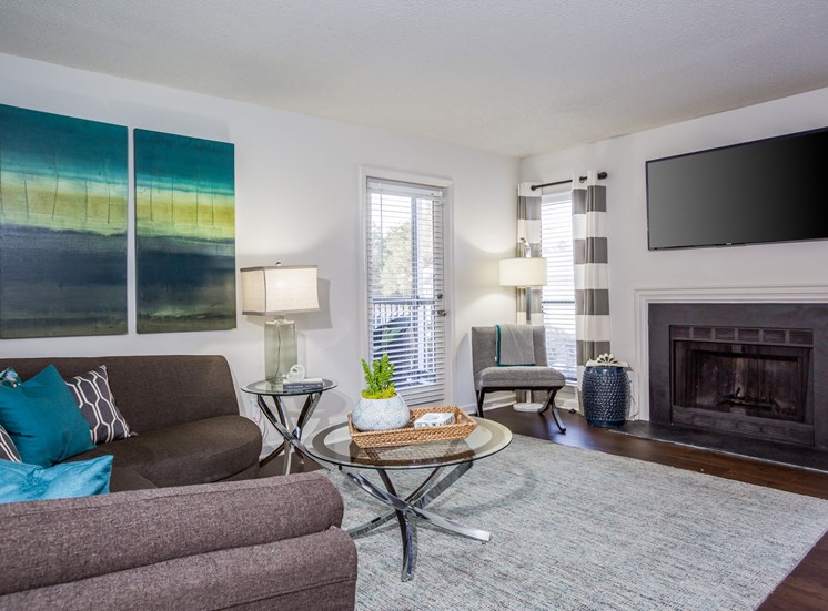 Model Living Room with Grey Couch on Area Rug And TV Mounted Above the Fireplace