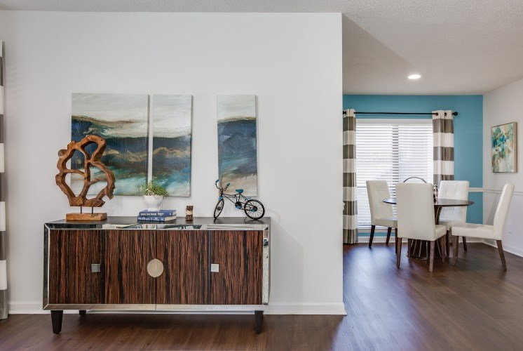 Model Apartment with Buffet with Decorations Against Wall with Art and Dining Table in the Background