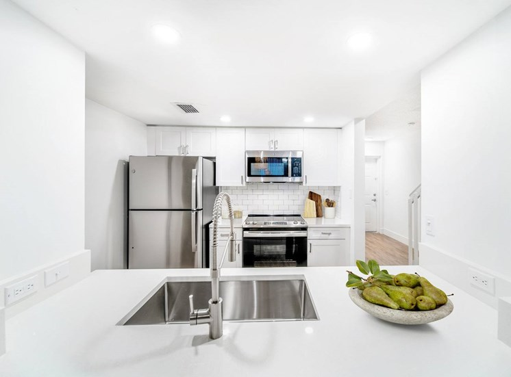 View of Kitchen Through Breakfast Bar with White Counters, Double Basin Sink, Stainless Steel Appliances, White Cabinets and Virtually placed Decorations