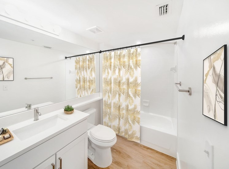 Bathroom with White Cabinets and Counters Next to Toilet and Tiled Shower with Virtually Place Shower Curtain and Decorations