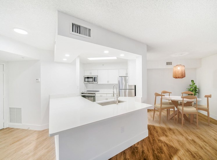 Kitchen with Breakfast Bar, White Counters and Cabinets, Stainless Steel Appliances  Next to Dining Room with Hardwood Style Flooring  and Virtually Placed Dining Table and Chairs