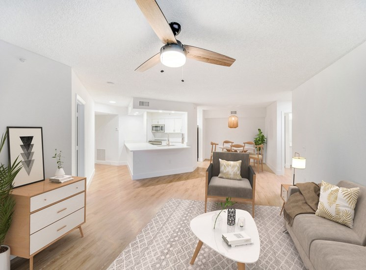 Open Floor Plan with Hardwood Style Flooring and Breakfast Bar off of Kitchen Next to Dining Room With Virtually Placed Dining Table and Cairs Behind Couch, Armchair and Coffee Table on Area Rug