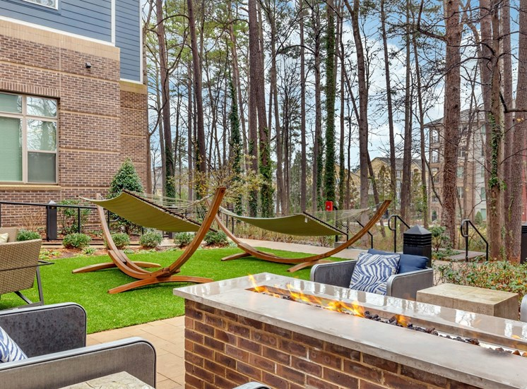 View of courtyard with large trees in the background, hammocks, and outdoor lounge chairs