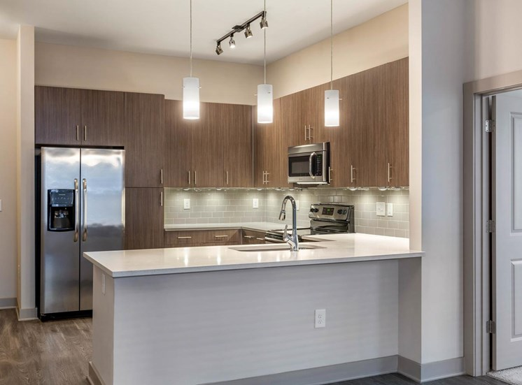 Kitchen with modern lights, wooden cabinetry,  brushed nickel appliances, and hardwood style flooring