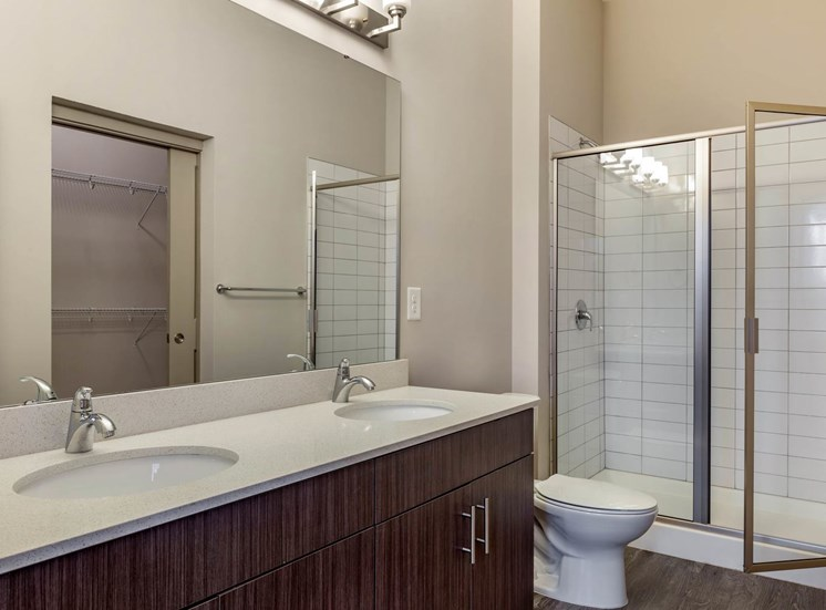 Bathroom with double vanity sinks, walk in shower, and large mirror