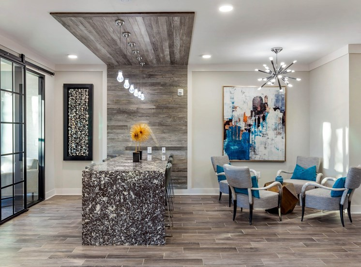 Clubhouse interior with hardwood style flooring, blue and white accents, and an island table