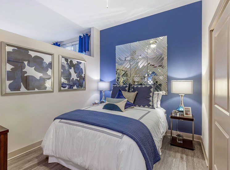 Furnished bedroom with blue accent wall, large framed art work, bedside table, and lamp