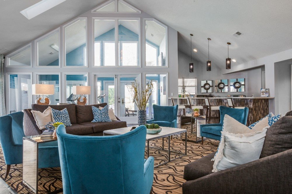 Clubhouse interior with vaulted ceilings, modern light fixtures, blue and tan accent colors, blue couches, and tan and black rug