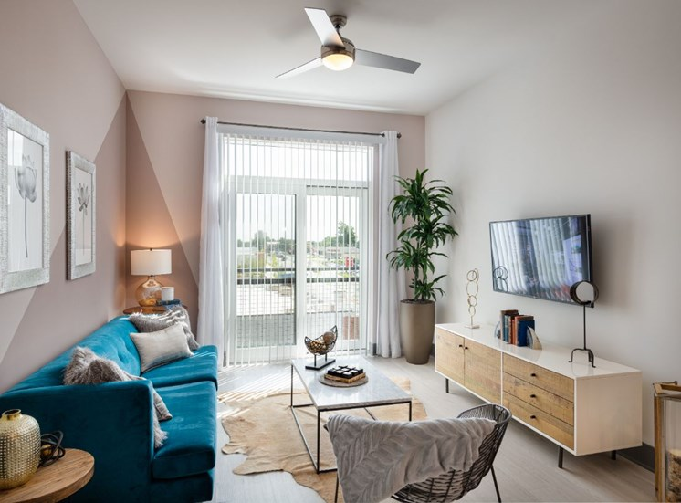 Model Living Room with Blue Couch Next to Sliding Glass Patio Door  Coffee Table on Area Rug Next to Entertainment Buffet Under Mounted TV