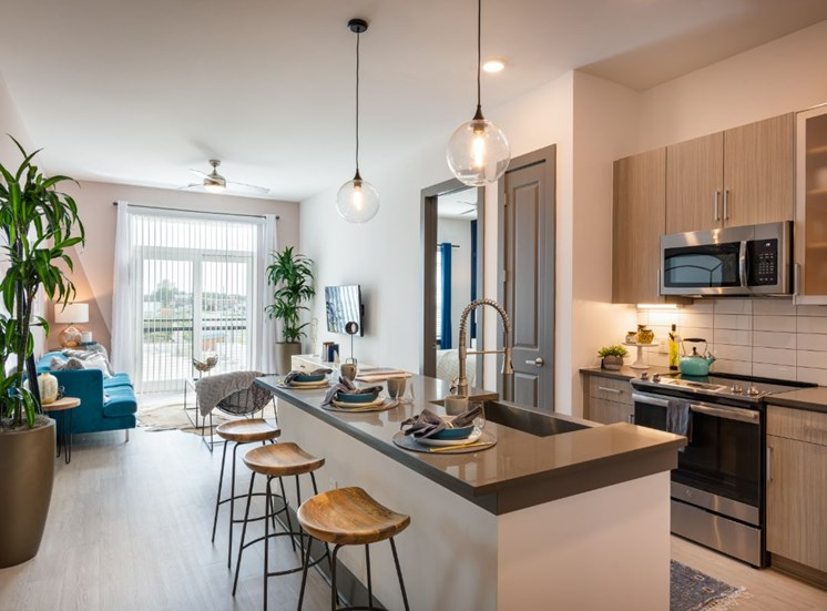 Model Apartment with Open Floor Plan with Kitchen Island Grey Counters Light Wood Cabinets and Stainless Steel Appliances Next to Living Room with Plants and Furniture