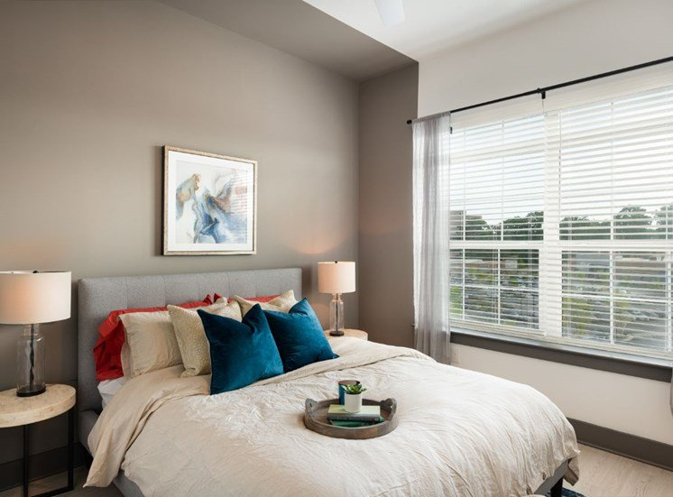 Model Bedroom with WIndow Bed with Accent Pillows and Shelf with Lamp
