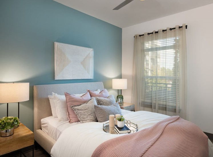 Model Bedroom with Light Blue Accent Wall with Art Above Headboard  with Nightstands on Either Side