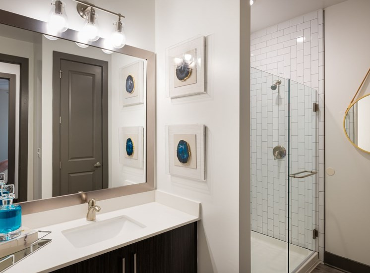 Model Apartment with Decorations on White Counter Under Framed Mirror Next to Walk in Shower