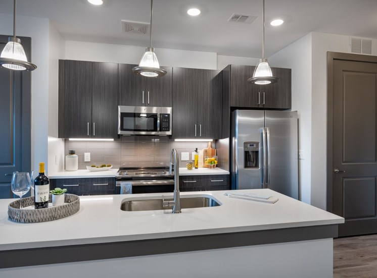 Model Kitchen with Stainless Steel Appliances Grey Wood Cabinets and Light Grey Counters with Kitchen Island