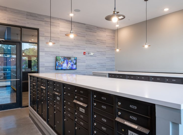 Mailroom with Mailboxes Under White Counters and Mounted TV