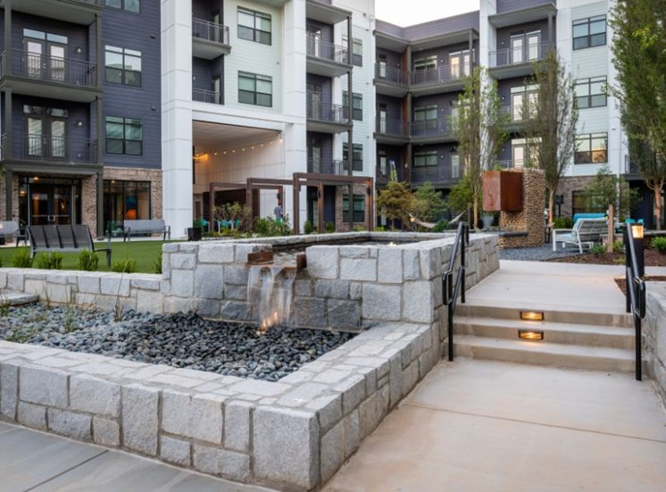 Waterfall Fountain in Front of Courtyard Between Buildings with Tables and Chairs Hammocks and Fireplace