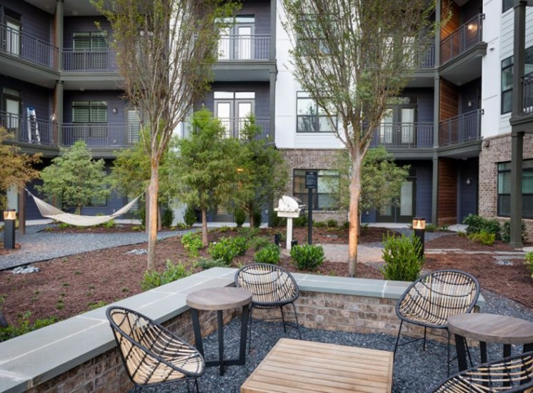 Courtyard Between Buildings with Tables and Chairs and Hammocks Between Trees