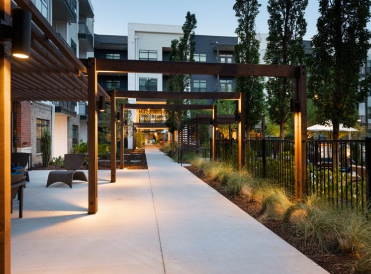 Sidewalk Next to Building With Pergola Beams Over Lighted Walkway to Building
