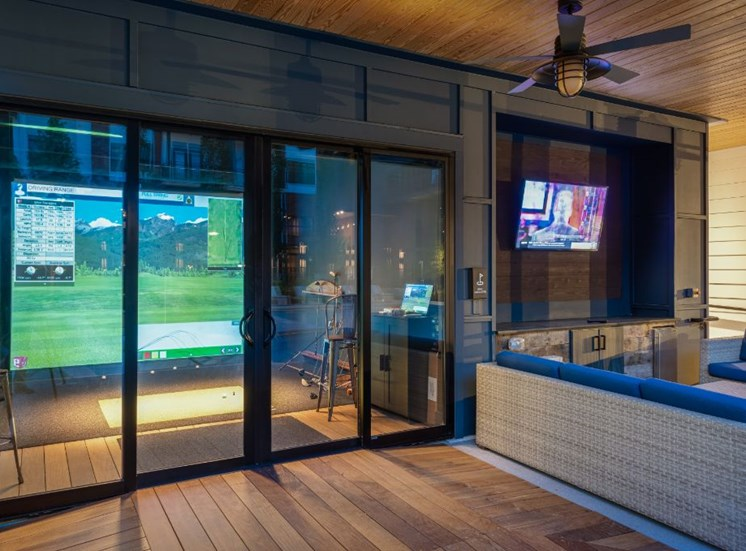 Indoor Virtual Golf Room with Glass Doors Next to Sectional Couch in Front of Mounted TV