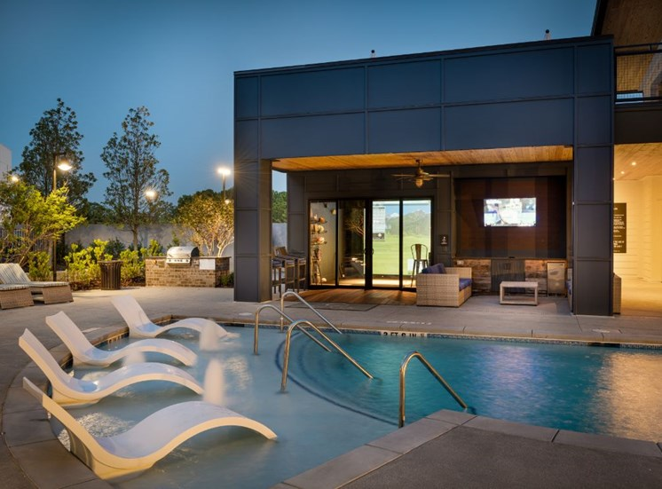 Swimming Pool with Lounge Seating Next to Virtual Golf Room with Glass Doors