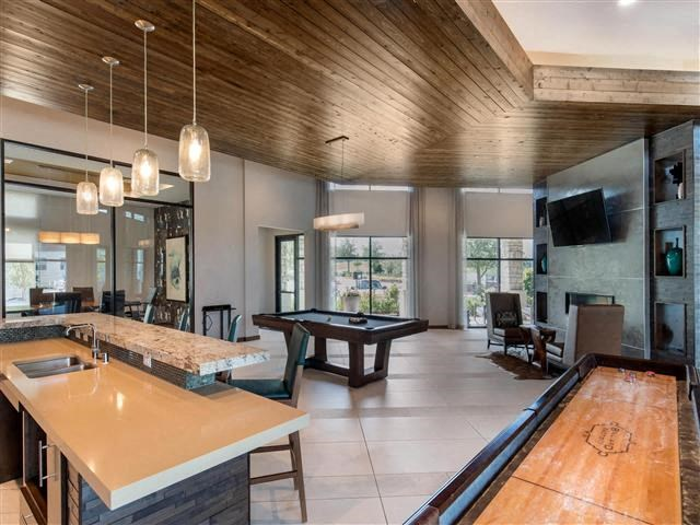 Game room with billiards table, clubhouse kitchen for entertaining, pool table, and wood panel ceilings