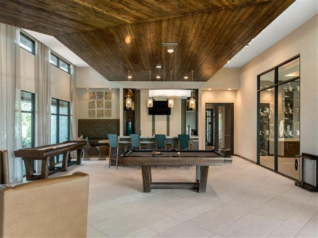 Billiards and Game Room with wood panel ceilings, white painted walls, and large windows overlooking the scenery