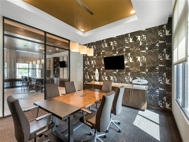 Conference Room with desk, 6 chairs, and a television mounted on the wall