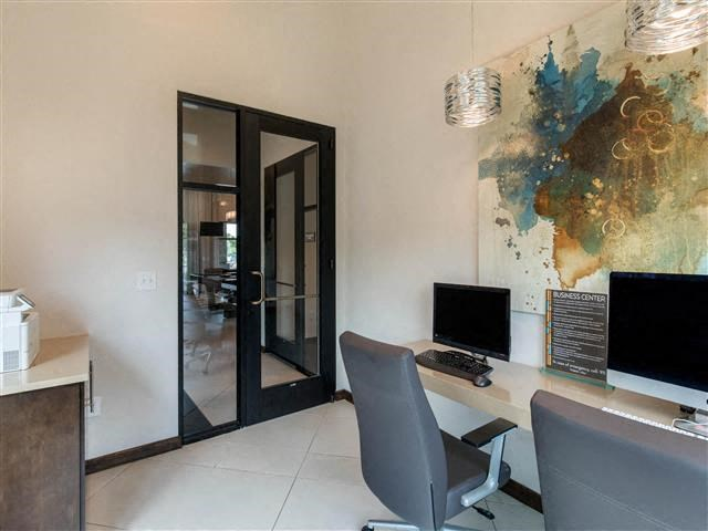 Business Center with two computers, two desks, and brown and teal modern painting, and a printer