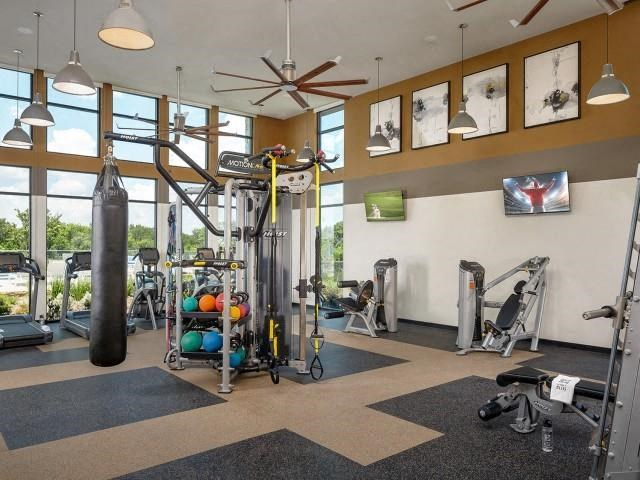 Strength and Cardio Studio fitness center with gray and tan flooring, ceiling fans, large windows, and medicine balls for working out