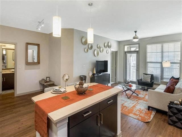 Kitchen interior with gourmet kitchen island, orange and tan color scheme, and hardwood style flooring with furniture