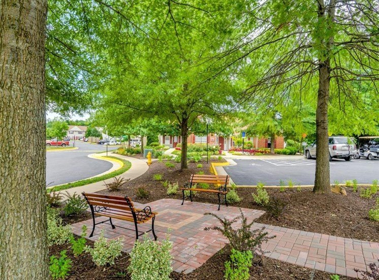 Community area with two park benches, stoned walkways, mature trees, plant beds with mulch and bushes with parking lot and driveway in the background