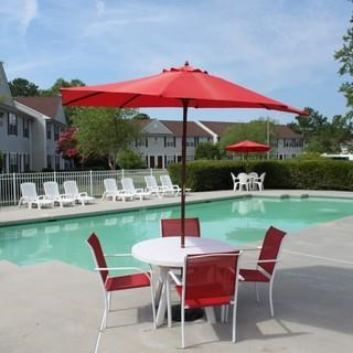 Umbrella With Table And Chairs Next To The Swimming Pool