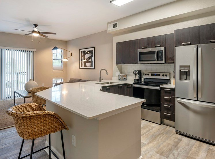 Model Kitchen with Wood Cabinets, Grey Counters, Stainless Steel Appliances and Breakfast Bar with Bar Stools