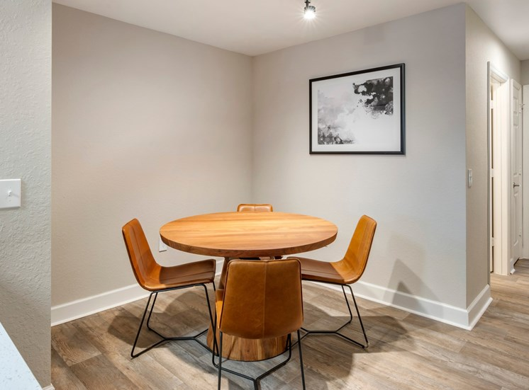 Model Dining Room with Dining Table Next to Art Hung on Wall
