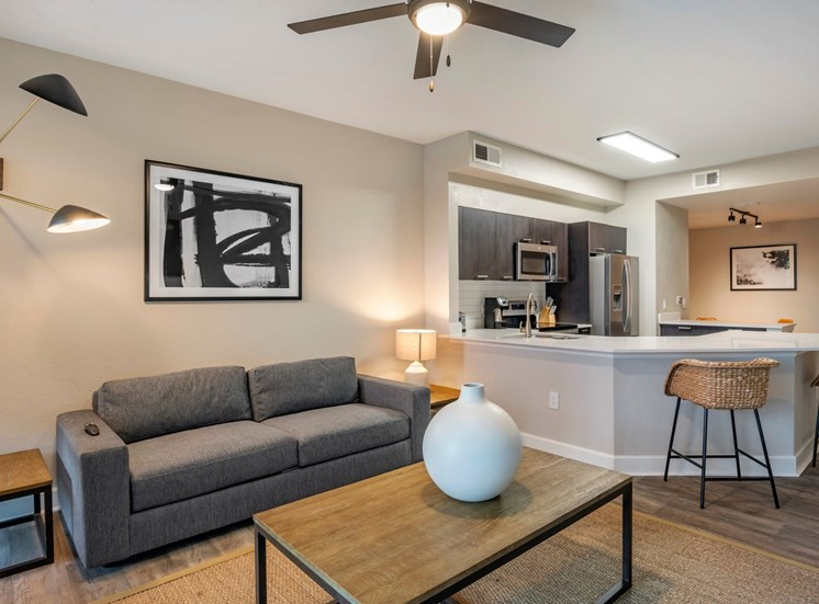 Model Living Room with Couch, Coffee Table and Decorations Connected to Kitchen with Breakfast Bar