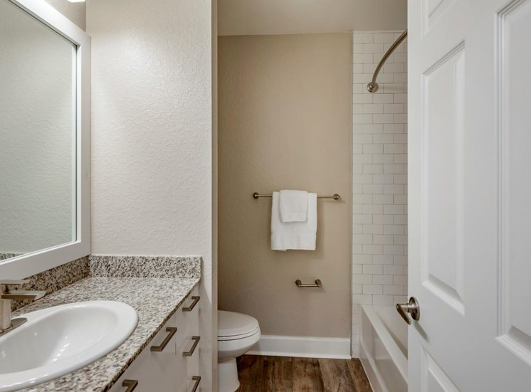 Model Bathroom with  White Cabinets, Grey Counter and Tiled Shower with Bathtub