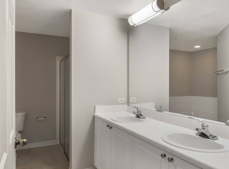 Bathroom with Double Sinks, White Counters and Cabinets Under Mirror