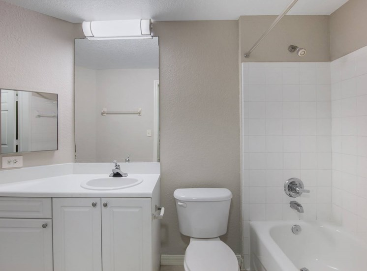 Bathroom with White Cabinets and Counters Next to Toilet and Tiled Shower
