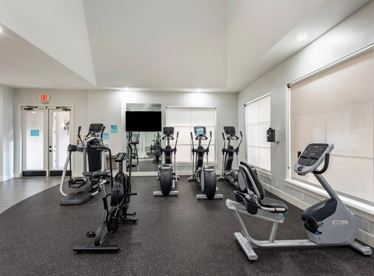 Bright Fitness Center with Covered Windows, Exercise Equipment and Mirrored Accent Wall with Mounted TV