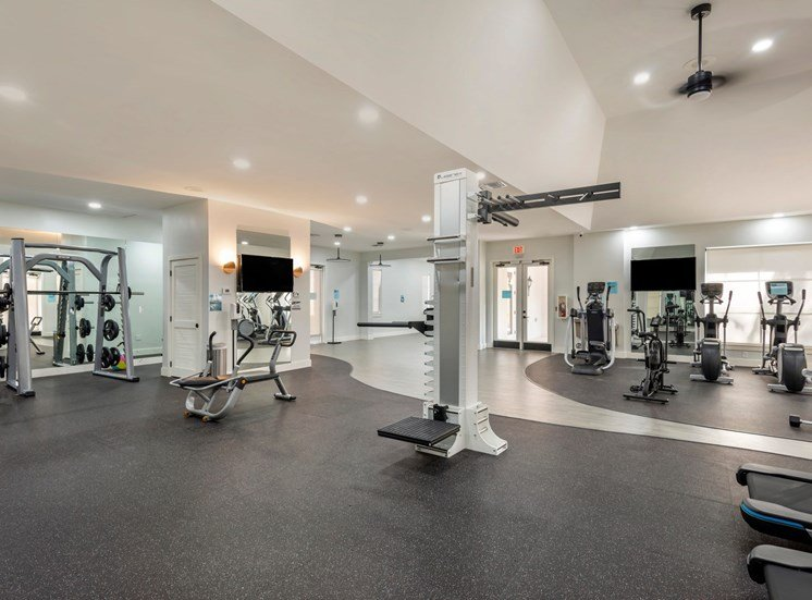 Bright Fitness Center with Covered Windows, Exercise Equipment and Mirrored Accent Walls with Mounted TVs