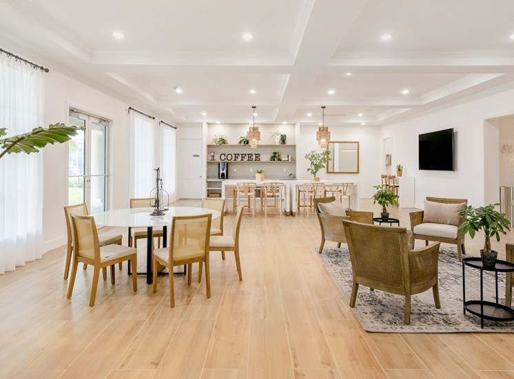 Community room table with eight chairs, table decor, kitchen area with coffee, fridge, shelves, sitting area with four chairs, table with six chairs, rug, two end tables and a tv