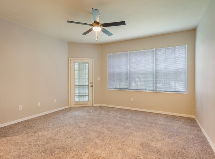Carpeted Room with Large Covered Windows Next to French Door