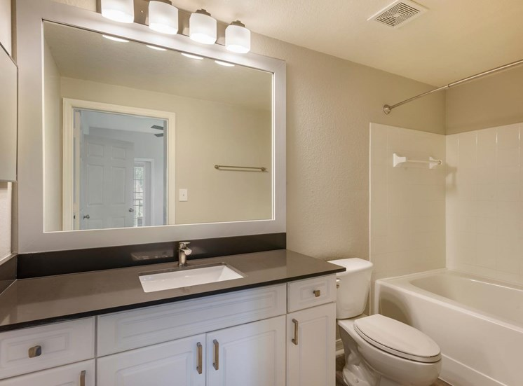 Bathroom with Grey Counters, White Cabinets, Toilet and Tiled  Shower